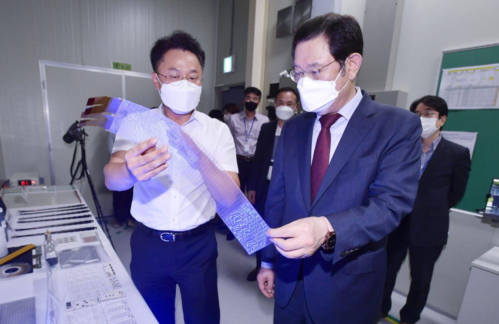 이용섭 광주시장(오룬쪽)이 김유신 티디엘 대표로부터 생산제품에 대한 설명을 듣고 있다.