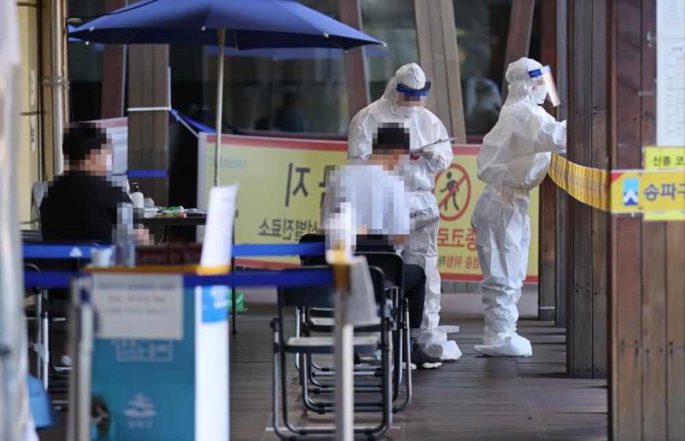 24일 오전 서울 송파구보건소에 마련된 신종 코로나바이러스 감염증(코로나19) 선별진료소에서 시민들이 문진표를 작성하고 있다. 연합뉴스
