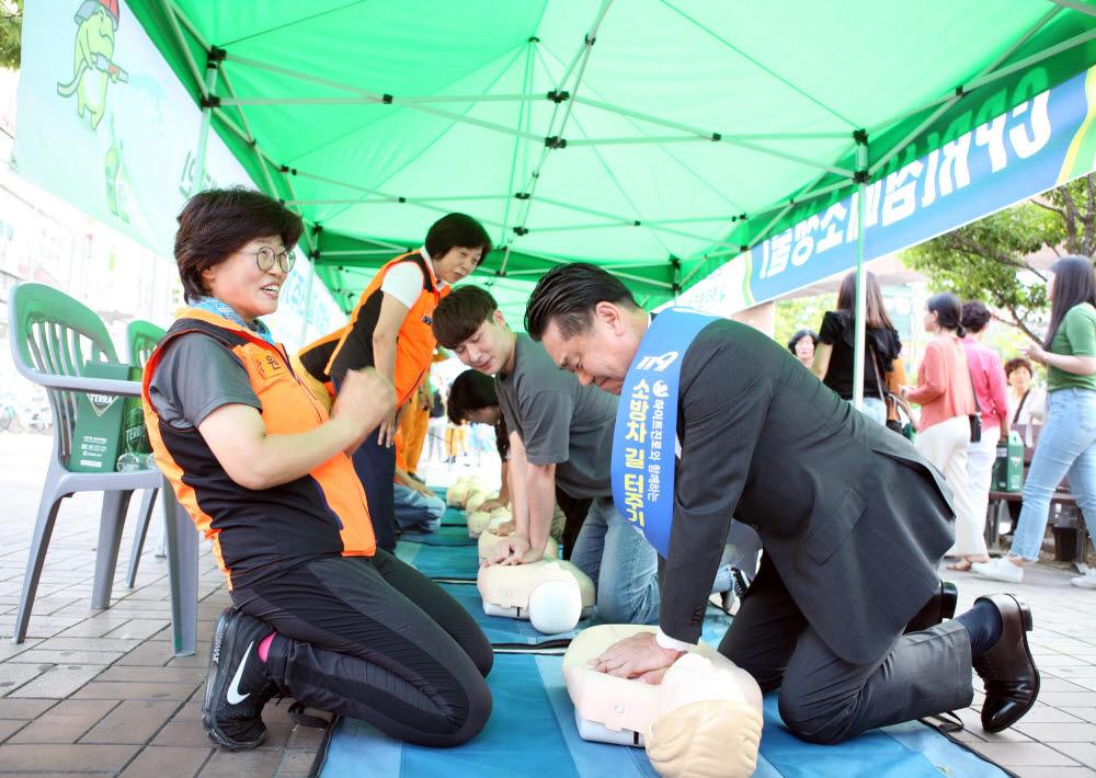 김인규 하이트진로 대표가 지난해 7월, 창원시 상남동 일대에서 진행한 국민안전캠페인에서 심폐소생술 체험을 하고 있다.