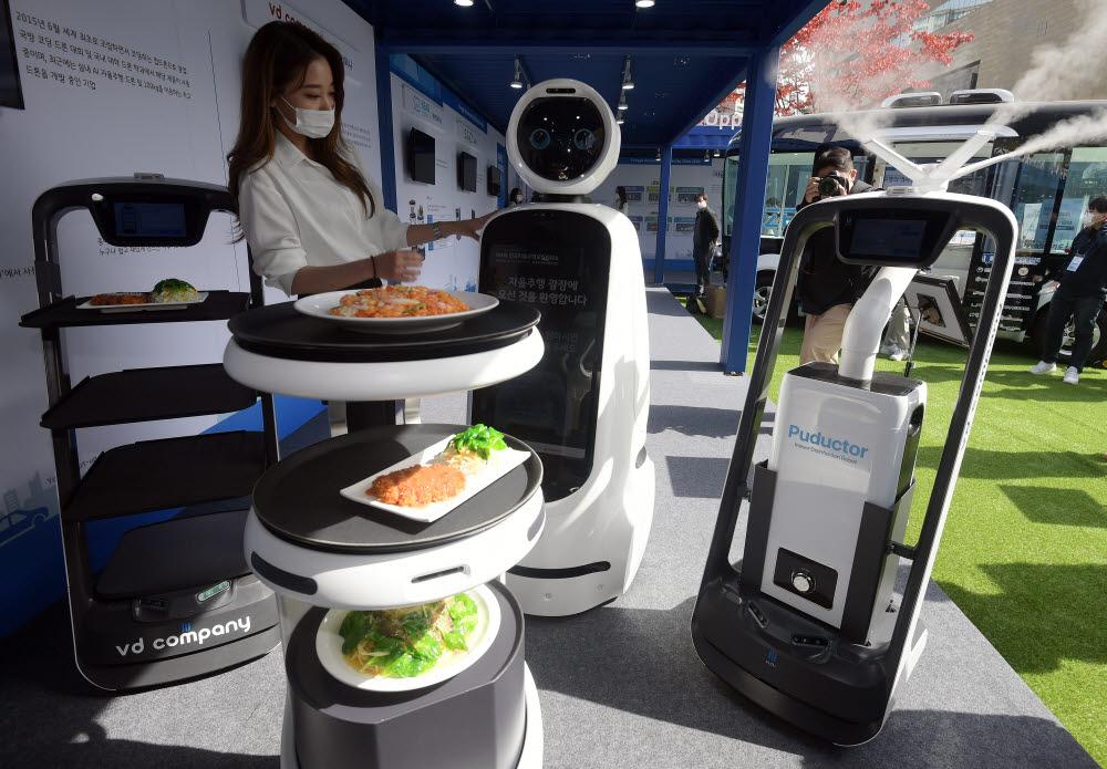 행사 관계자가 다양한 자율주행 로봇을 선보이고 있다. 왼쪽부터 브이디컴퍼니의 서빙로봇 푸두봇, 베어로보틱스의 서빙로봇 서비, LG전자의 안내로봇 클로이, 브이디컴퍼니의 소독로봇 푸닥터.