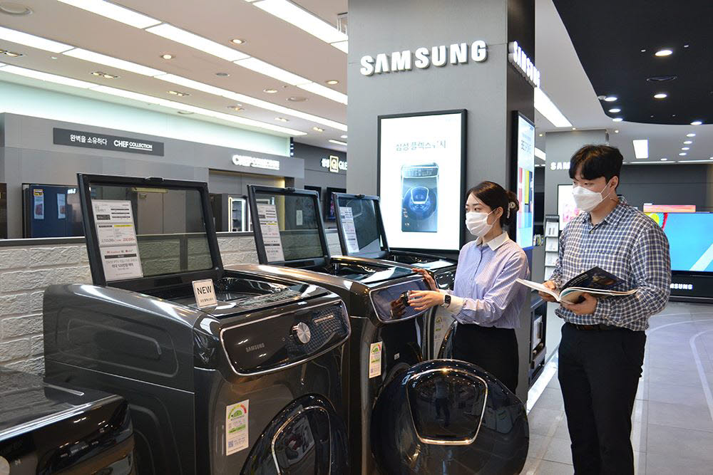 전자랜드 매장에서 고객들이 대용량 드럼세탁기를 살펴보고 있다.
