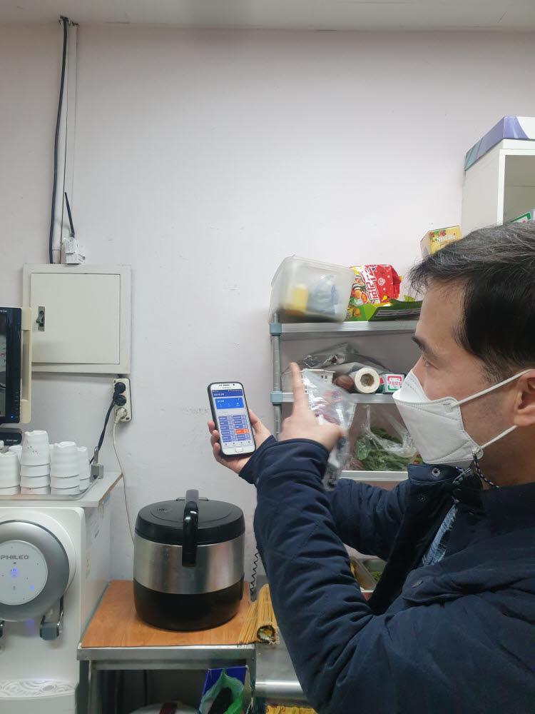 대전 중앙시장에 있는 분식집에 스마트폰보다 작은 전기상태감지센서가 설치되어 있다. 벽에 설치된 단말기에서 나오는 정보를 에프에스 직원이 스마트폰으로 확인하고 있다.