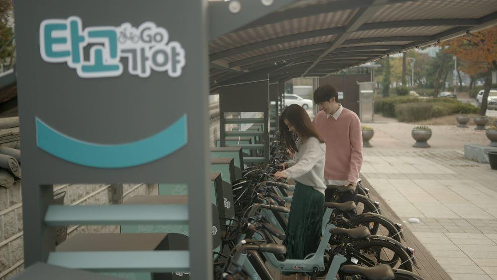 시민들이 무선충전 전기자전거 거치대에서 자전거를 이용하는 모습. 사진=김해시