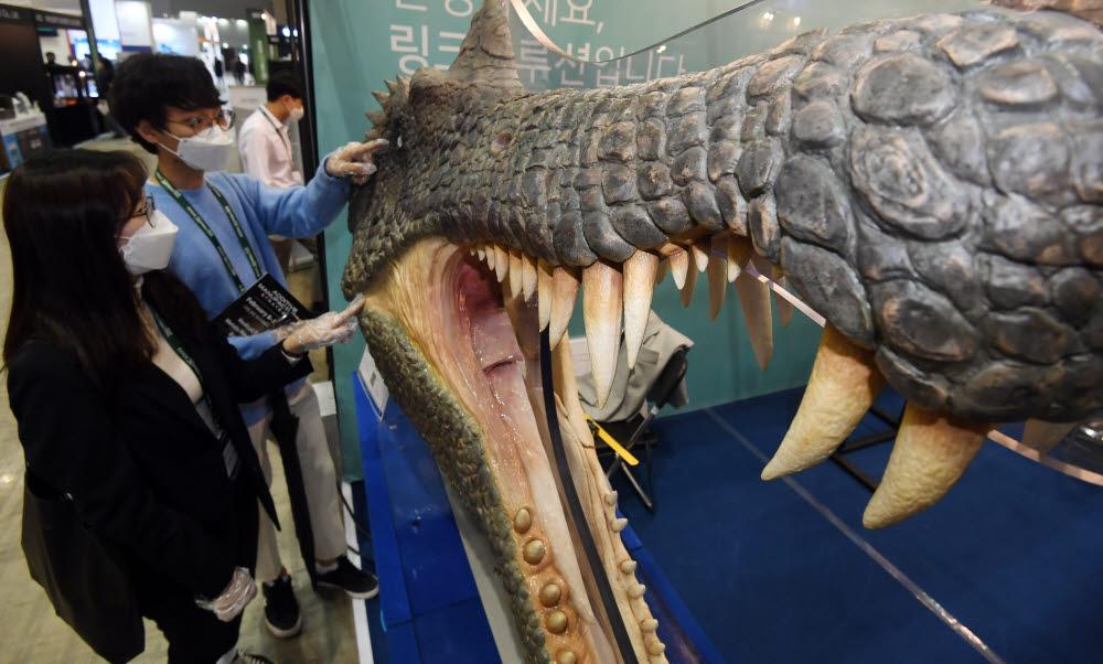 참관객이 링크솔루션의 초대형 3D프린터로 제작한 공룡 모형을 살펴보고 있다.