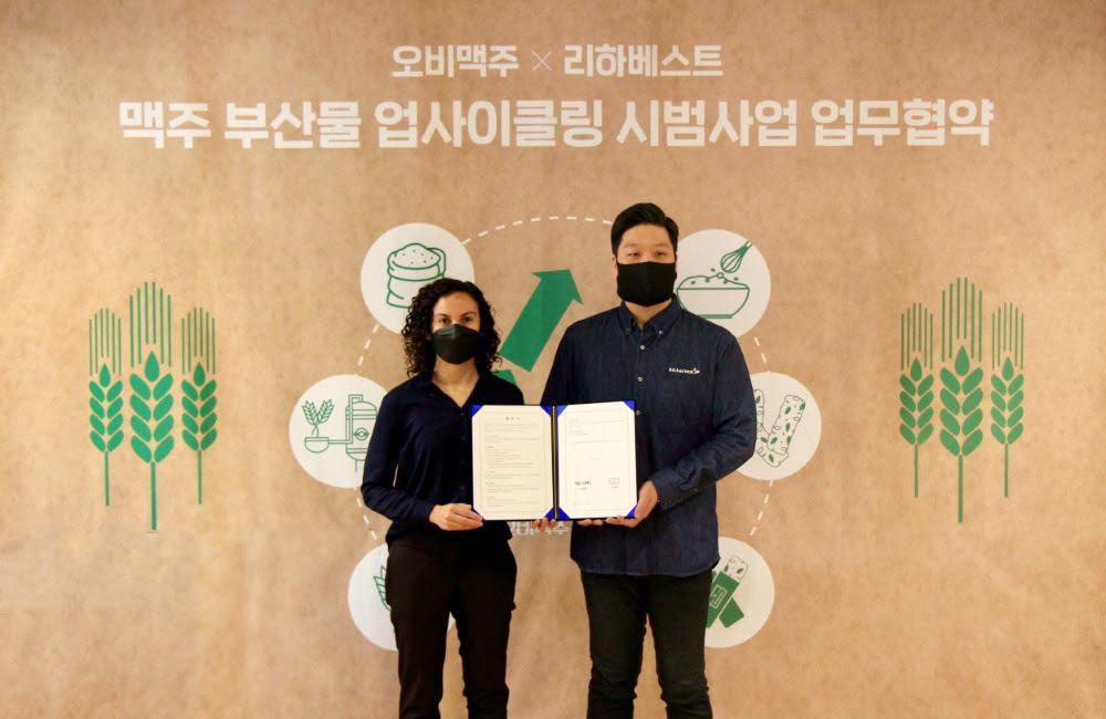 나탈리 보르헤스 오비맥주 구매·지속가능경영 부문 부사장(왼쪽)과 민명준 리하베스트 대표가 맥주 부산물 업사이클링 사업을 위한 상생 협약을 맺고 기념촬영했다.