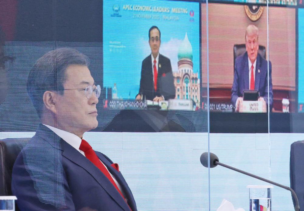 문재인 대통령이 20일 오후 청와대에서 열린 아시아태평양경제협력체(APEC) 정상회의에서 의장국인 말레이시아의 무히딘 야신 총리 개회사를 듣고 있다. 문 대통령 뒤로 도널드 트럼프 미국 대통령의 모습도 보인다. 연합뉴스