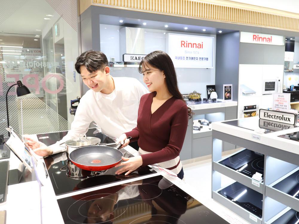 롯데하이마트 매장에서 고객들이 전기레인지를 살펴보고 있다.