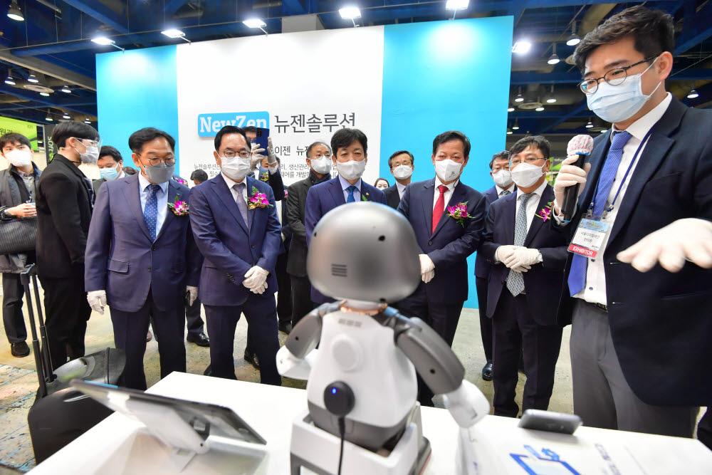 서울시 부스에서 로봇 활용 시니어 디지털 교육에 활용하는 휴머노이드 로봇 리쿠에 대한 설명을 듣고 있다.
