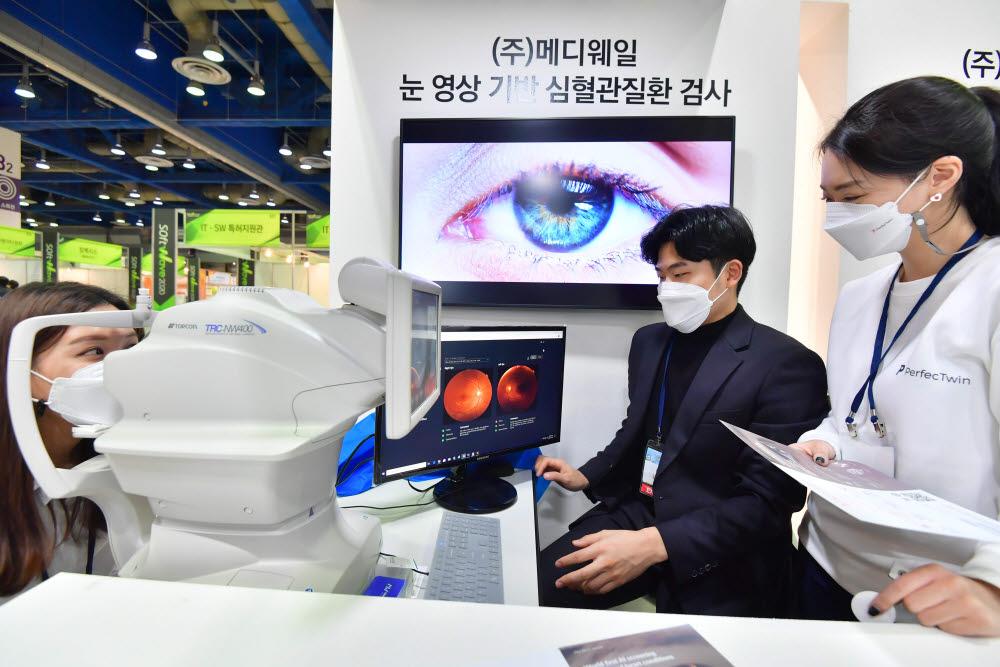 서울시 부스 메디웨일에서 관람객이 눈 영상 기반 심혈관질환 검사를 받고 있다. 박지호기자 jihopress@etnews.com