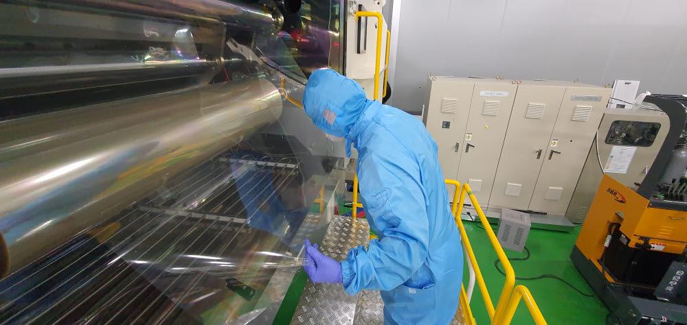 엠에스웨이 직원이 플라스틱 기반의 박막태양전지용 유연 투명전극을 생산하고 있다.