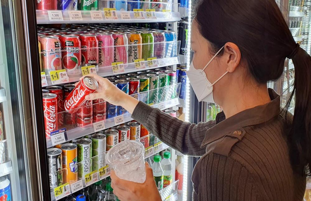 고객이 이마트24 매장에서 얼음컵과 음료를 구입하고 있다.