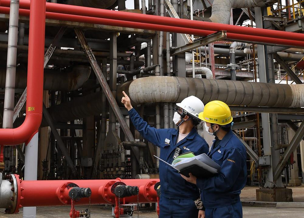 에쓰오일 공장 직원들이 스마트헬멧을 착용하고 현장을 이동하며 설비를 점검하고 있다. [자료:에쓰오일]