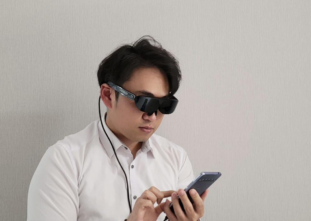 TCL MOLED G는 스마트폰과 연결해 100인치대 화면으로 영상이나 VR 콘텐츠 등을 감상할 수 있다.