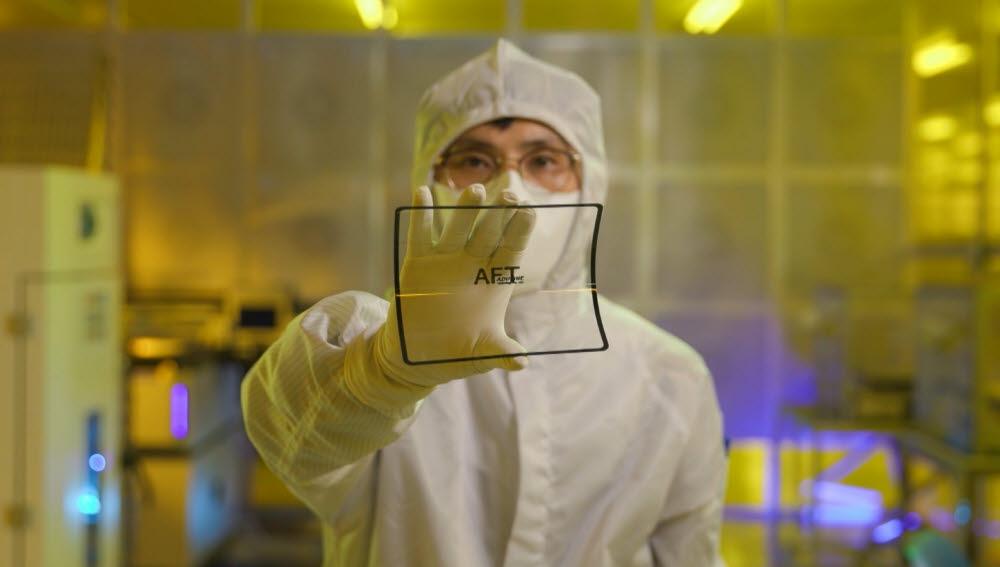 애드파인테크놀러지 연구원이 초박판유리에 PDR을 코팅한 제품을 들어보이고 있다.