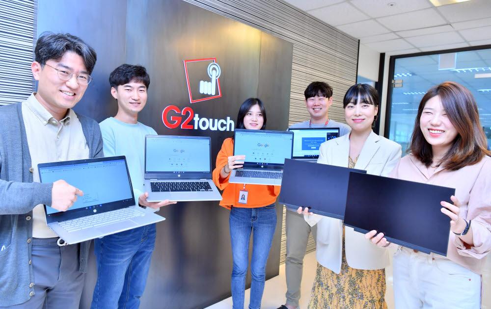 지2터치 직원들이 대면적 터치스크린과 노트북을 들어보이고 있다.<사진=전자신문DB>