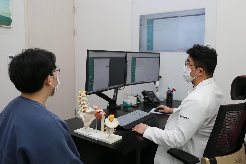 정종훈 힐링본 정형외과 원장이 이지케어텍의 클라우드 전자의무기록(EMR) 엣지앤넥스트를 사용해 환자를 진료하고 있다. (사진=이지케어텍)