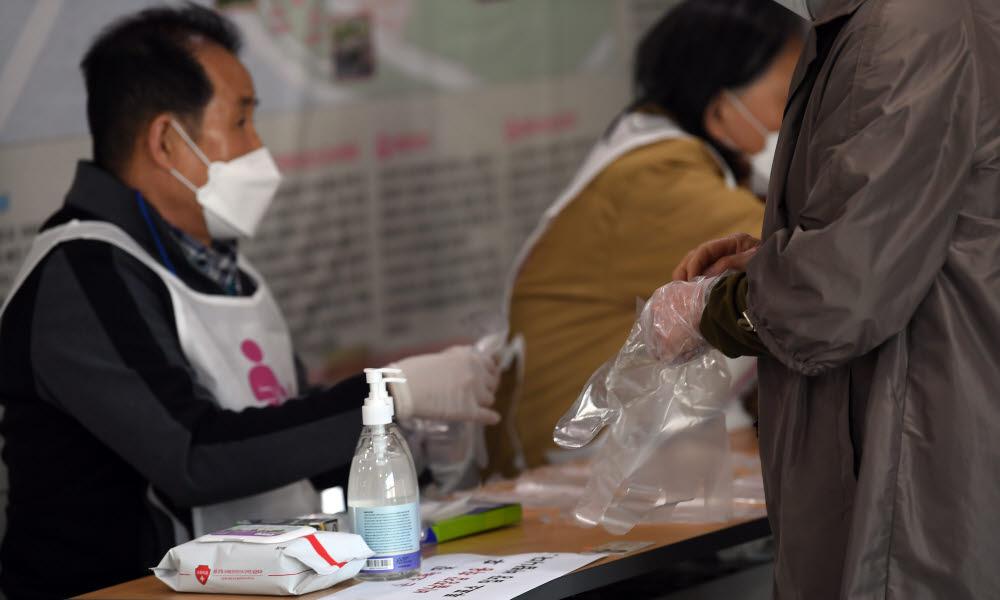 4·7재보궐 선거일인 7일 오전 서울 마포구 합정동주민센터에 마련된 합정동 제3투표소에서 유권자들이 입장 전 발열체크를 하고 있다. 이동근기자 foto@etnews.com