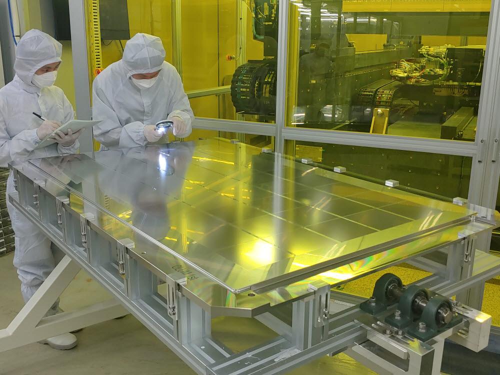 오럼머티리얼 연구원들이 OLED 증착에 사용되는 파인메탈마스크를 살펴보고 있다.<사진=오럼머티리얼>