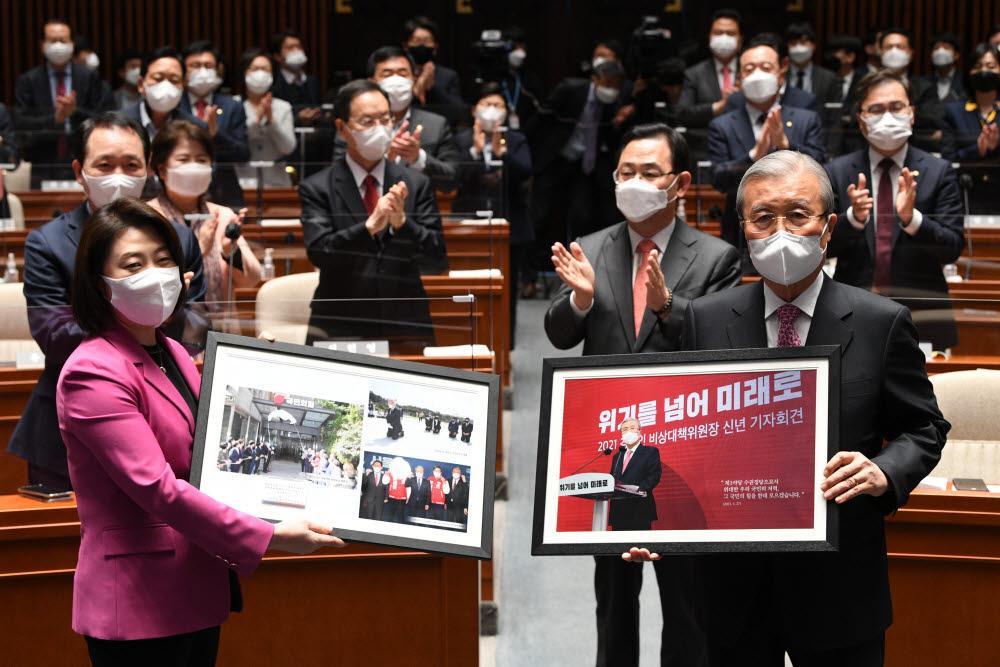 4.7 재·보궐선거를 마지막으로 국민의힘을 떠나는 김종인 비상대책위원장이 8일 오전 서울 여의도 국회에서 열린 의원총회에 참석, 기념액자를 받고 있다. <사진=연합뉴스>