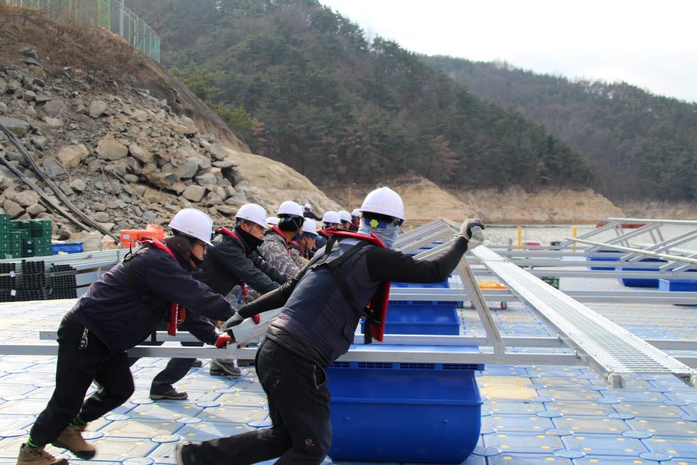 합천댐 수상태양광 설치 인력들이 구조체 조립을 하고 있다.