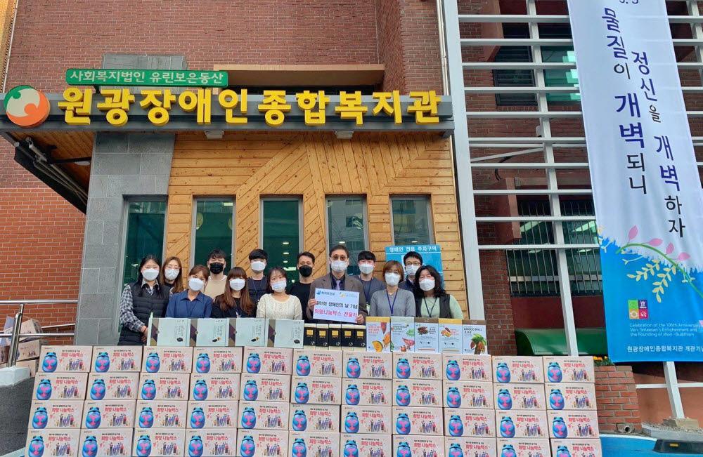 하이트진로는 원광장애인복지관에 희망나눔박스를 전달하고 김선기 관장(앞줄 오른쪽 세번째)을 포함한 직원들이 기념촬영을 진행했다.