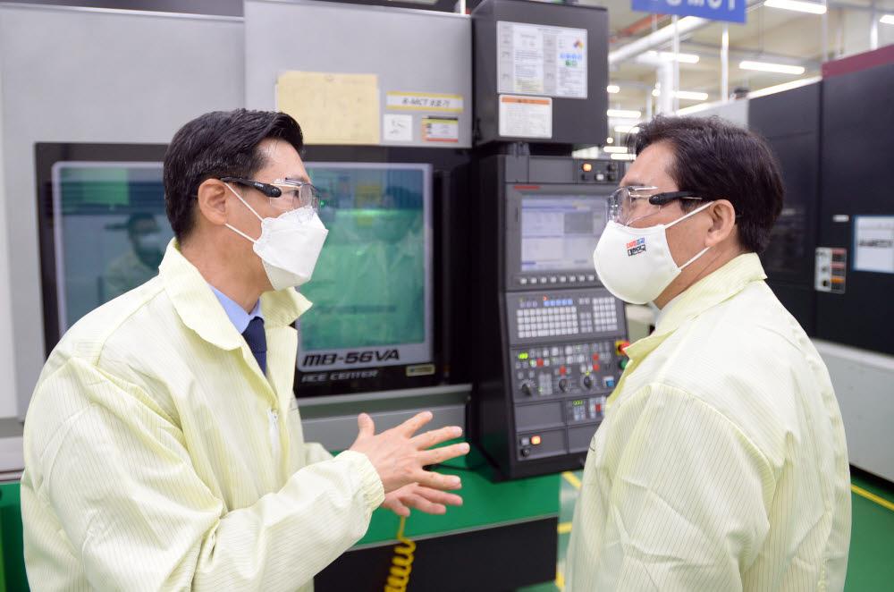 성윤모 산업통상자원부 장관(오른쪽)이 여문원 미코세라믹스 사장에게 생산공정에 대한 설명을 듣고 있다.