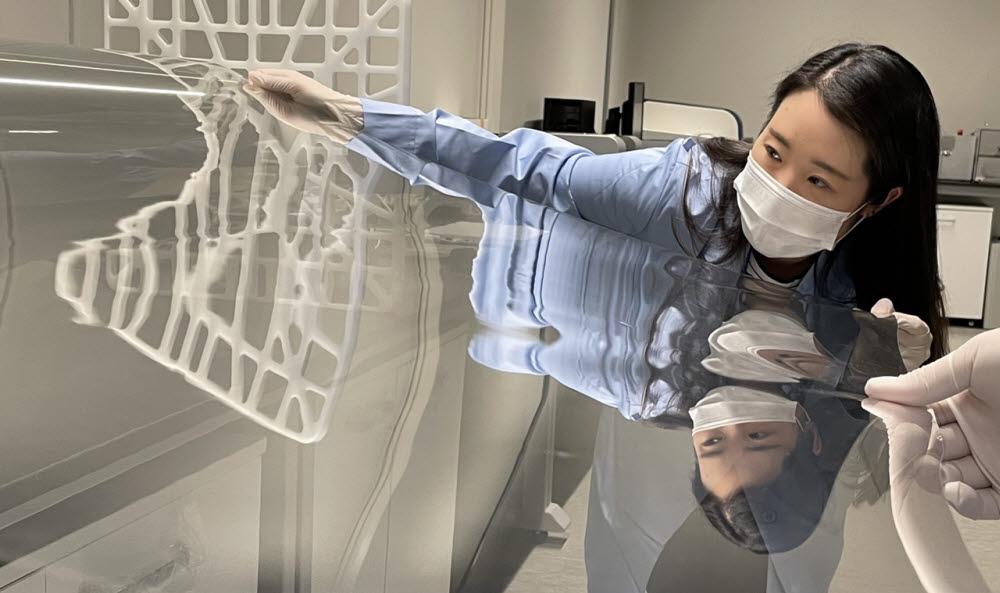 코오롱인더스트리 연구원이 샤오미폴더블폰 미믹스 폴드에 적용된 투명 폴리이미드 필름(CPI)을 점검하고 있다.<사진=코오롱인더스트리>
