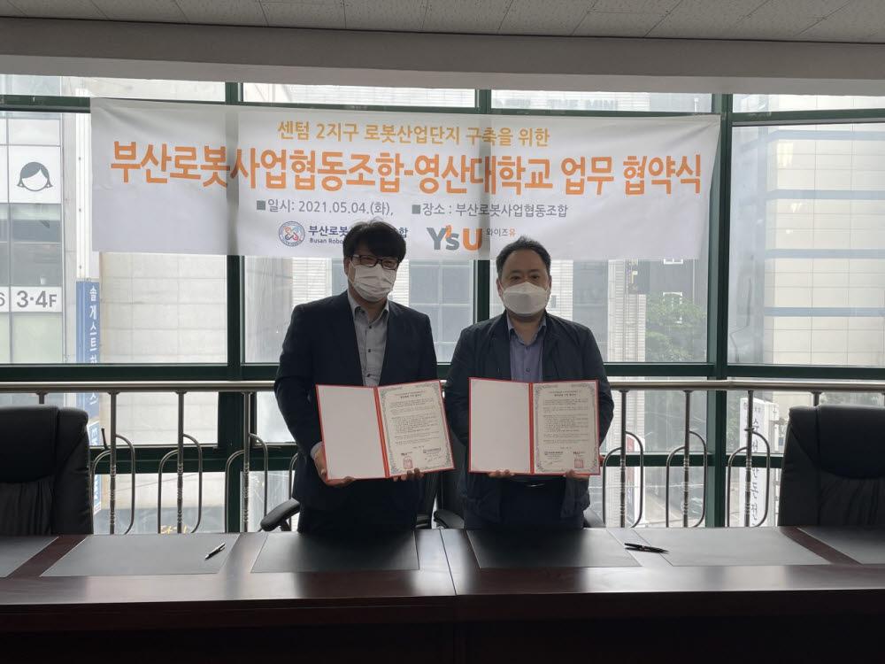 류현제 부산로봇사업협동조합 사무국장(왼쪽)과 김근수 영산대 산학협력단장이 업무 협약 후 기념 촬영했다.