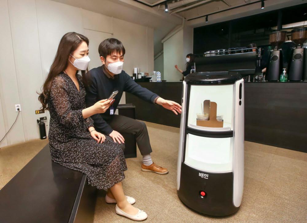 D타워 광화문에서 배달로봇 딜리타워로 커피 배달을 시연하고 있다.