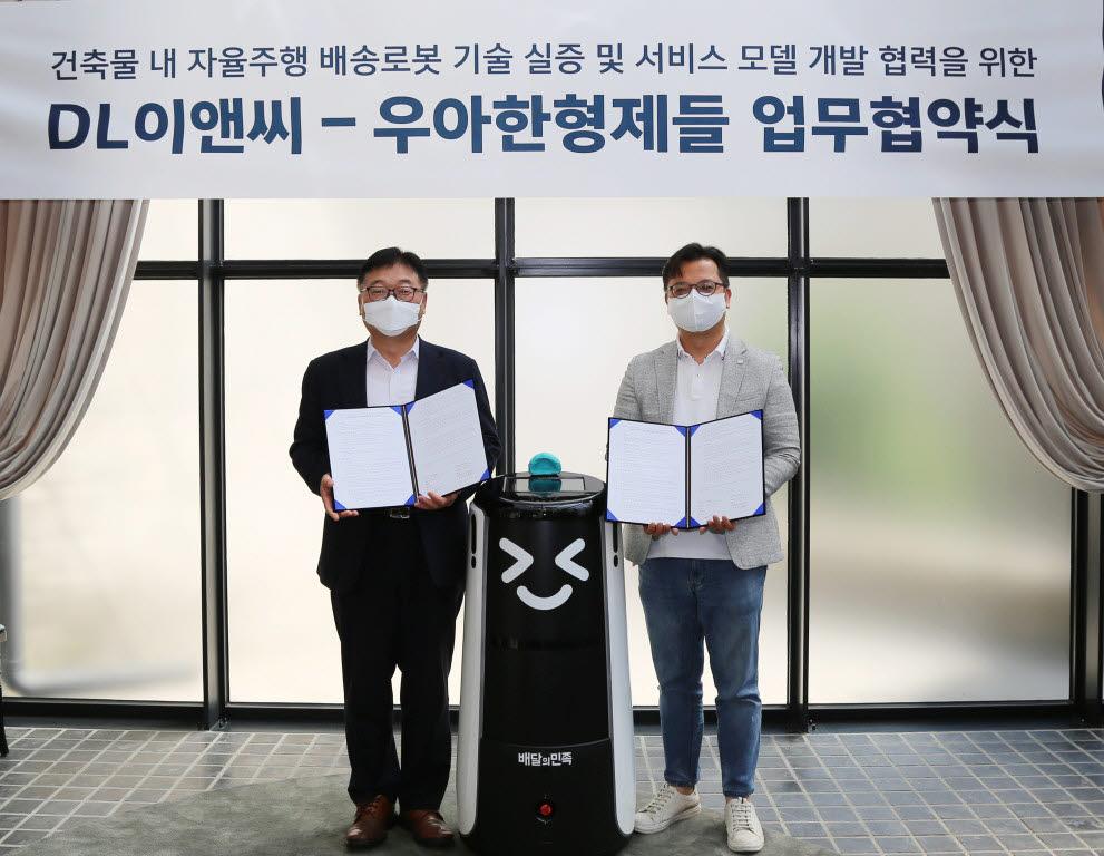 김요섭 우아한형제들 실장(오른쪽)이 나재현 DL이앤씨 실장과 13일 건물 내 배송로봇 기술 실증 및 서비스 모델 개발 협력을 위한 업무협약서(MOU)를 교환하며 기념 촬영을 하고 있다.