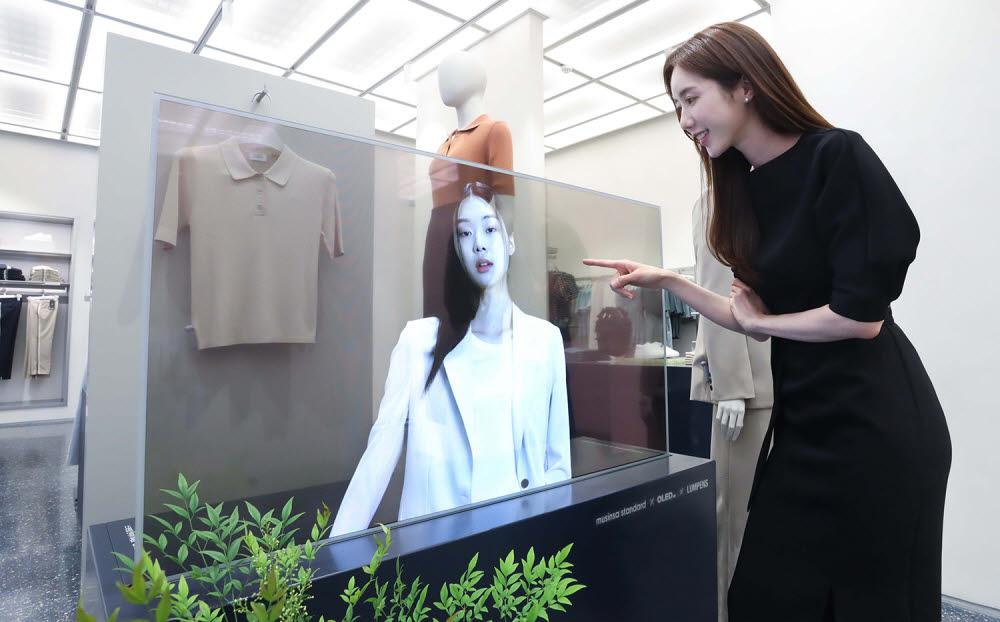 서울 마포구에 위치한 무신사 스탠다드 홍대에서 LG디스플레이 모델이 투명 OLED로 신상 의류를 확인하고 있다.(사진=LG디스플레이)