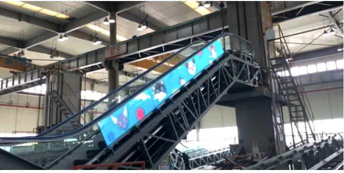 일본 후지테크의 생산라인에서 에스컬레이터 유리면에 필름형 투명 LED 디스플레이를 부착한 후 에스컬레이터를 작동하는 모습.