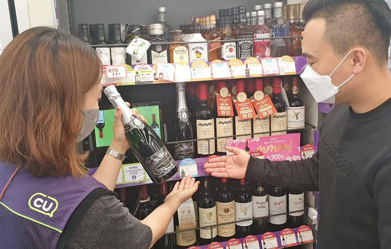 CU 와인샵을 통해 와인을 구매하러 온 고객에게 매니저가 상품에 대한 설명을 하고 있다