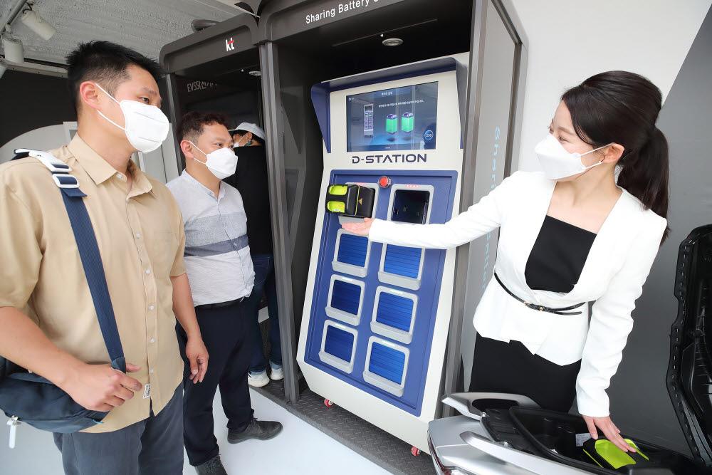 관람객이 KT 모빌리티 서비스 플랫폼 존에서 배터리 교환 플랫폼(BSS, Battery Swapping System)을 체험하고 있다.