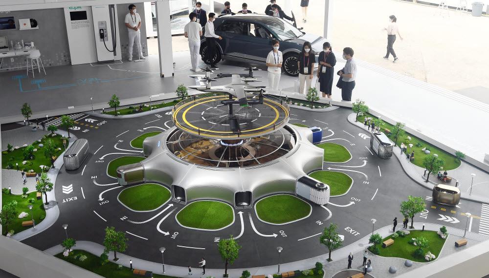 참관객들이 현대자동차부스에서 UAM과 지상 모빌리티를 연결하는 에코시스템을 살펴보고 있다.