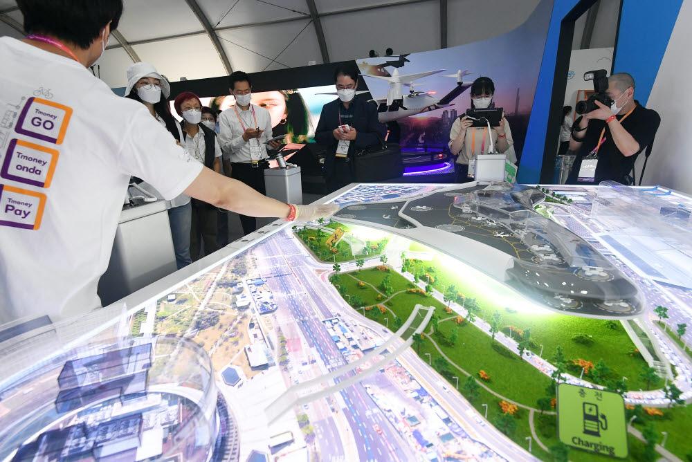참관객들이 미래 모빌리티 복합환승 허브 모형을 살펴보고 있다.