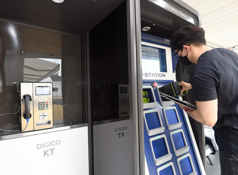 참관객이 KT부스에서 배터리교환플랫폼에서 교체형 배터리를 꺼내고 있다.