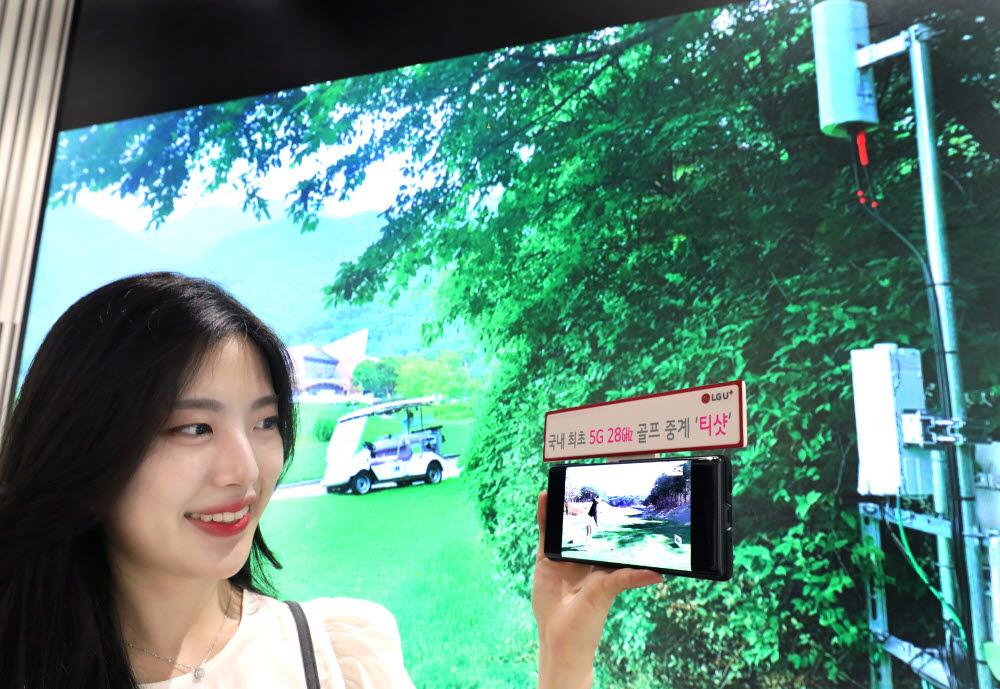 LG유플러스 모델이 레인보우힐스CC에 구축된 5G 28㎓ 기지국 현장 사진을 배경으로 U+골프 서비스를 감상하는 모습