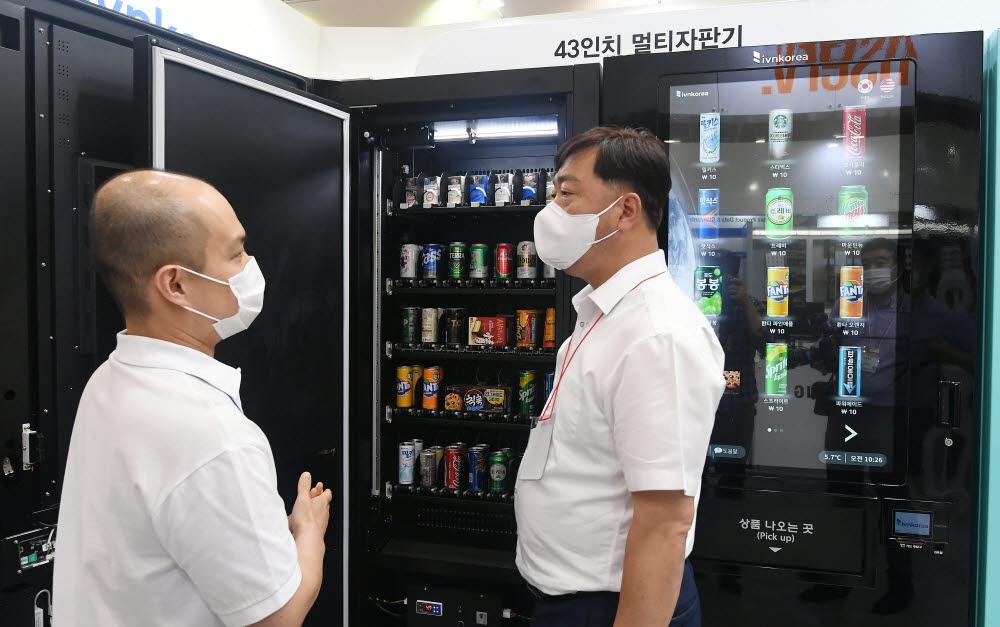 참관객들이 아이브이엔코리아 부스에서 다양한 멀티자판기를 살펴보고 있다.