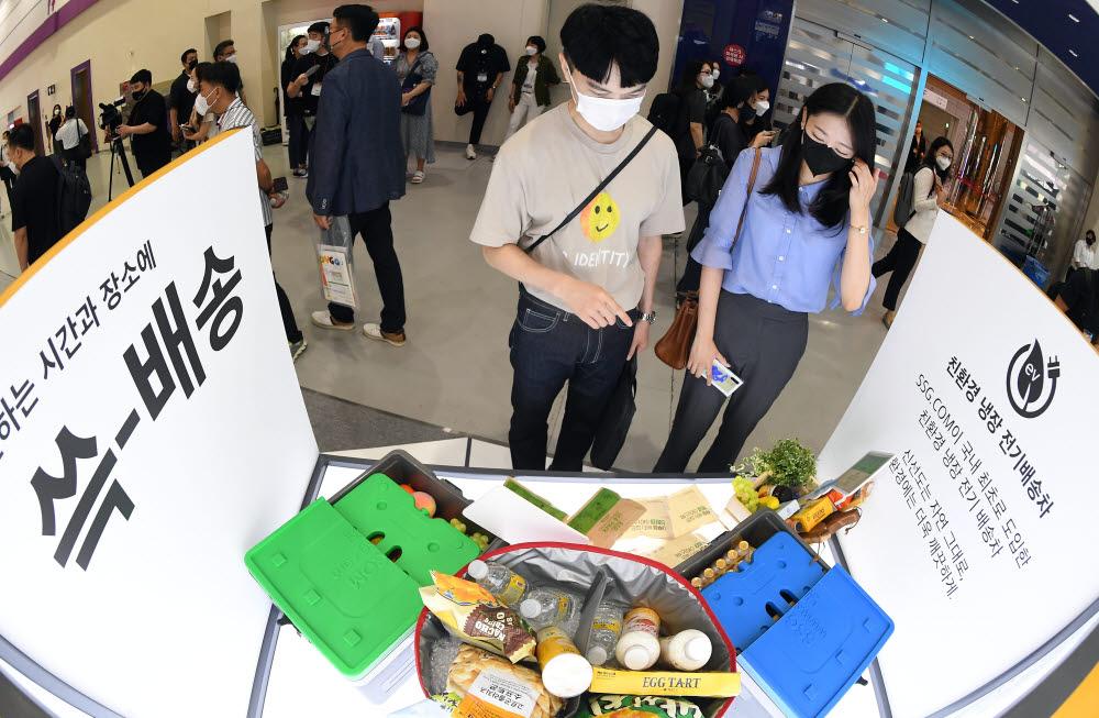 참관객들이 SSG닷컴 부스에서 친환경 냉장 전기배송차를 살펴보고 있다.