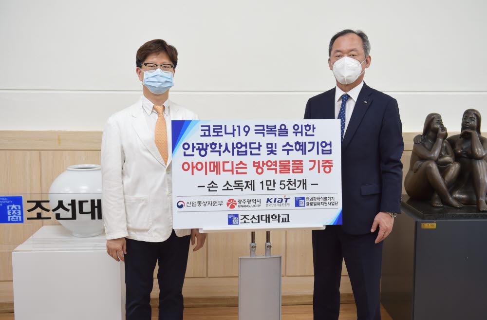 민영돈 조선대 총장(오른쪽)이 이동필 아이메디슨 대표로부터 학생 보건 안전을 위해 휴대용 손소독제 1만5000개를 기증받고 있다.
