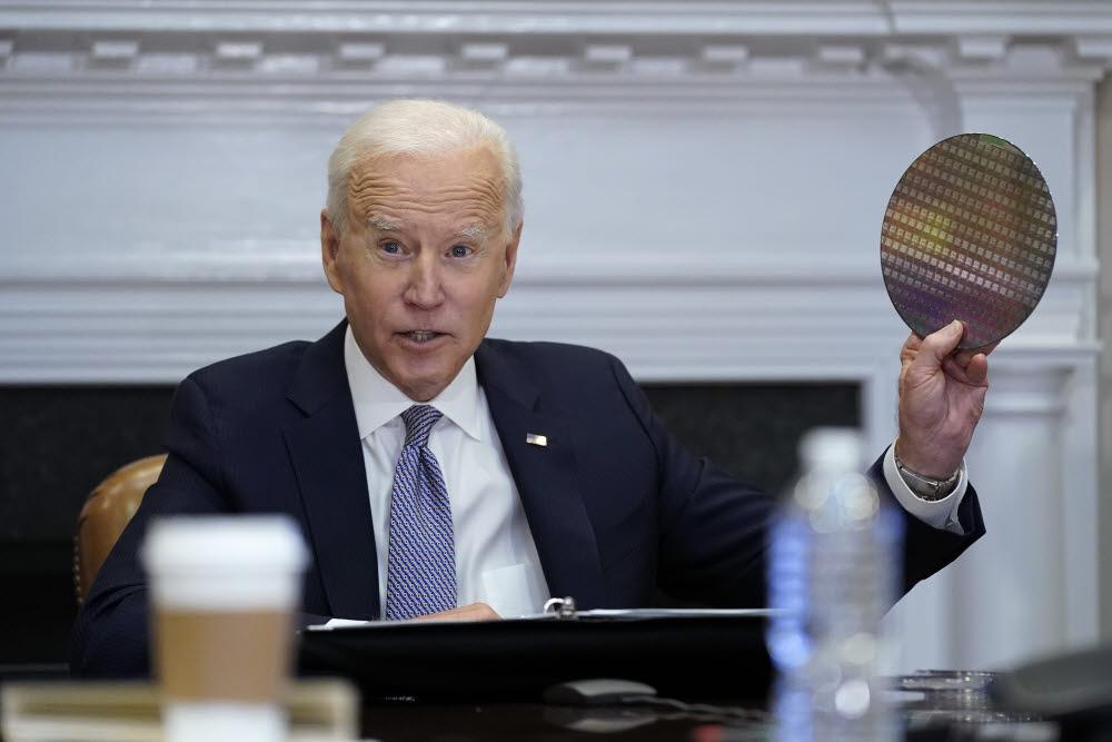 조 바이든 미국 대통령이 지난 4월 12일(현지시간) 워싱턴 백악관에서 열린 반도체 화상회의에서 반도체 웨이퍼를 들어 보이고 있다. 삼성전자·인텔·GM 등 반도체·자동차산업 관련 19개 글로벌 기업이 화상회의에 참석했다. <AP=연합>