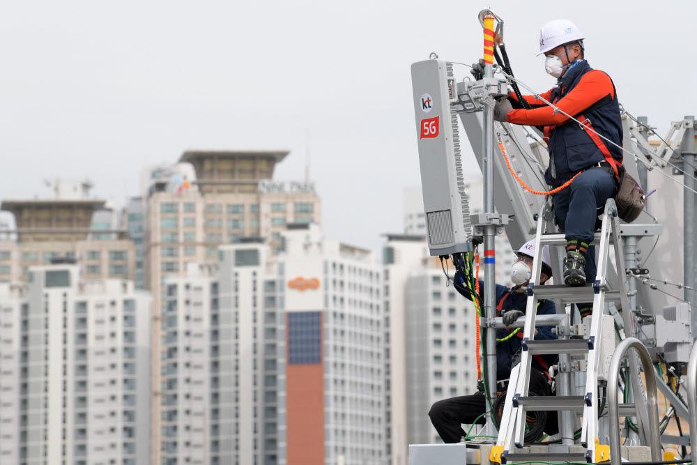 이동통신사 관계자가 아파트 옥상에 5G 기지국을 구축하고 있다.