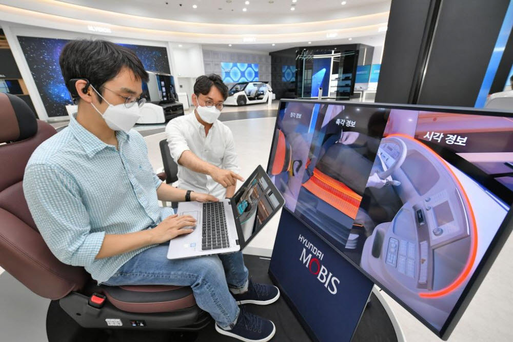 현대모비스가 세계 최초로 개발한 뇌파 측정 기반 운전자 모니터링 시스템 엠브레인을 개발한 연구원들이 관련 기술을 시험하는 모습.