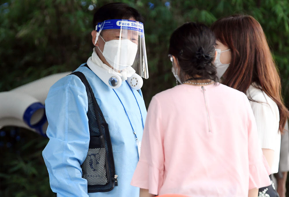 한 의료진이 더위를 피하기 위해 얼음조끼를 착용하고 시민들을 안내하고 있다.