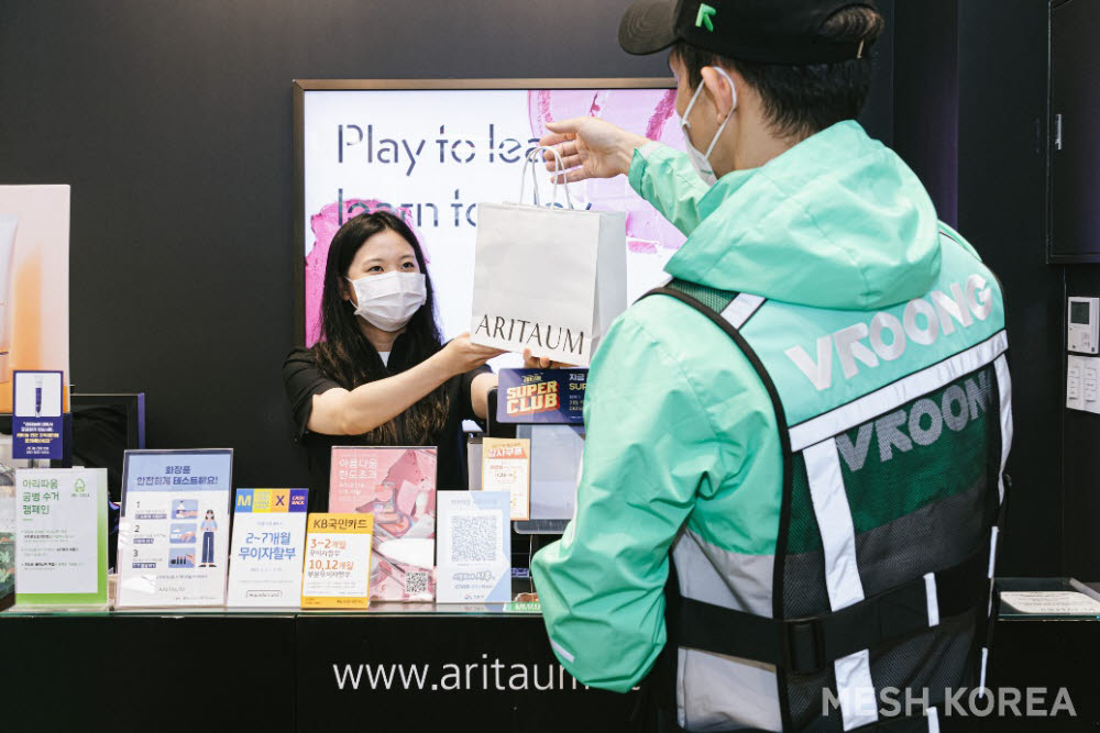 메쉬코리아가 운영하는 부릉 라이더가 뷰티 편집숍 아리따움에서 주문상품을 수령하고 있다.