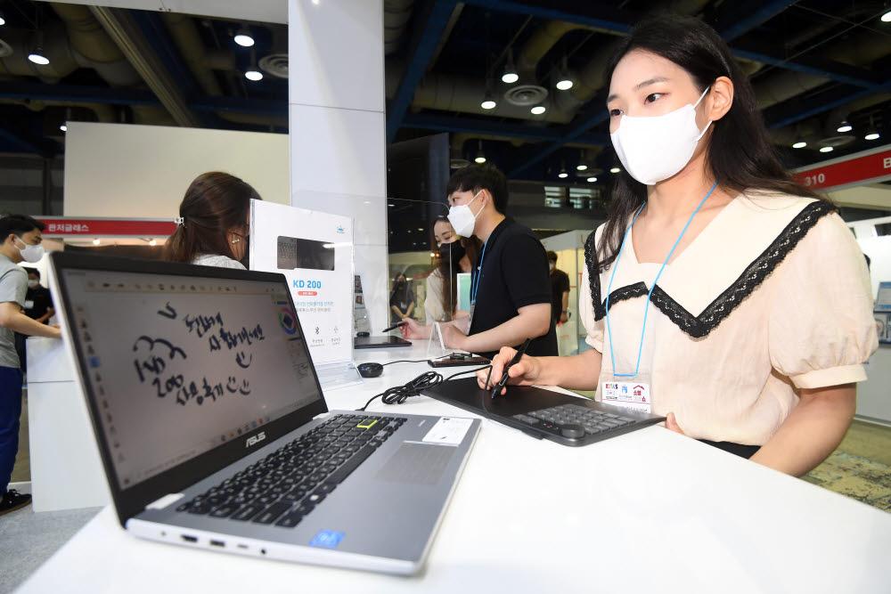 참관객이 그래픽 입력장치 제조사 휴이온의 블루투스 무선 펜타블렛 체험을 하고 있다.