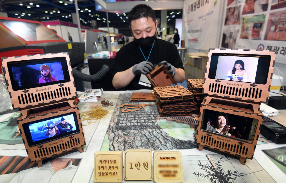 해광레이저 관계자가 레이저커팅으로 만든 스마트폰 미니 TV거치대를 조립하고 있다.