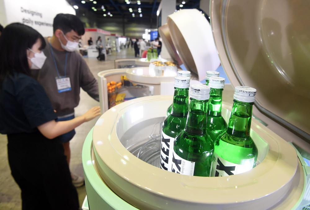참관객이 가정용 냉장고 전문기업 고모텍의 소형냉장고 꼬모냉장고 홈바를 살펴보고 있다.