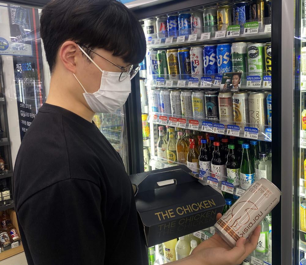 고객이 GS25에서 쏜살치킨과 맥주등을 구매하고 있다.